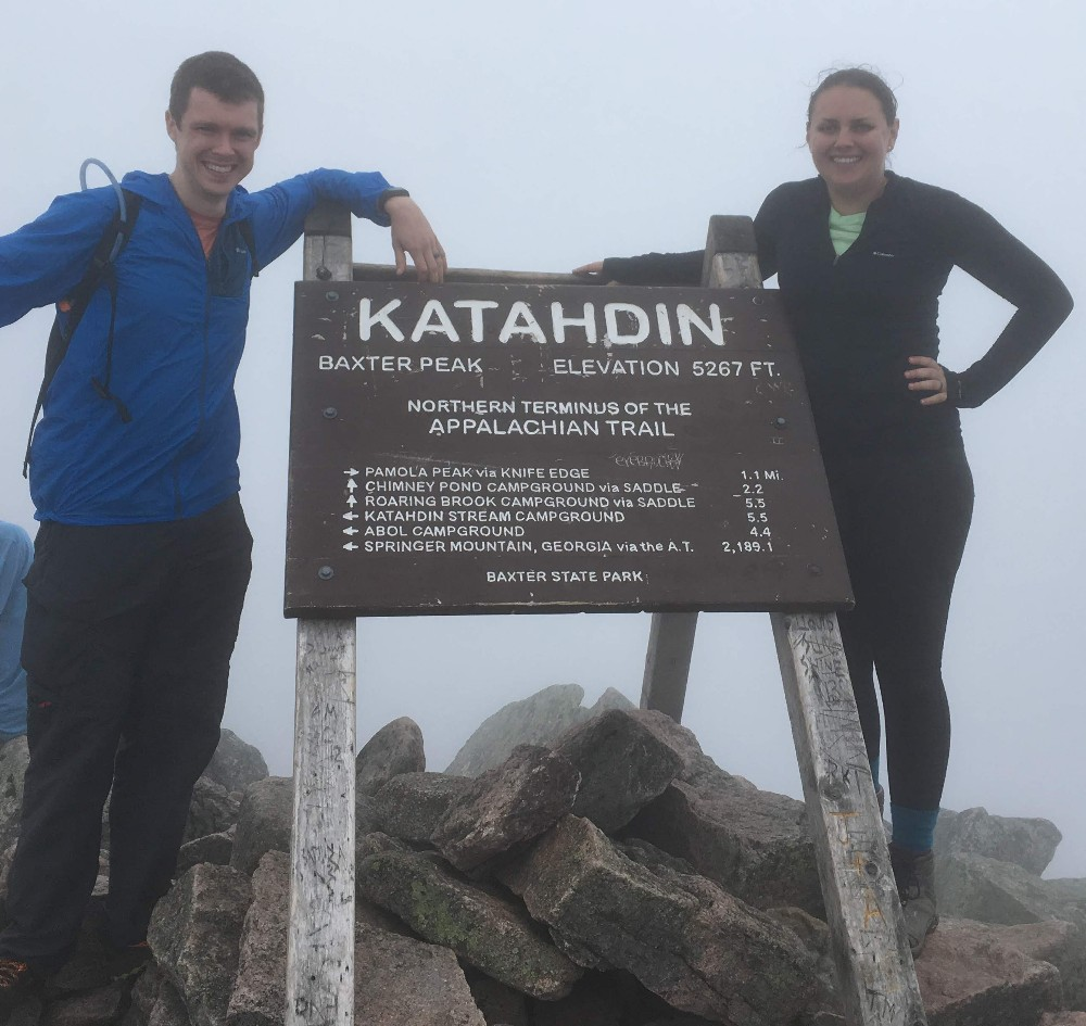 A man and a woman stand in the fog next to a sign marking Katahdin's peak